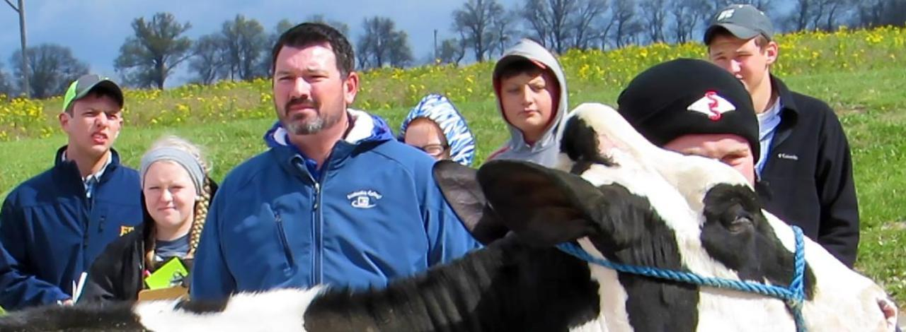 KC Ag Professor Aaron Heinzmann with students and cow for dairy program