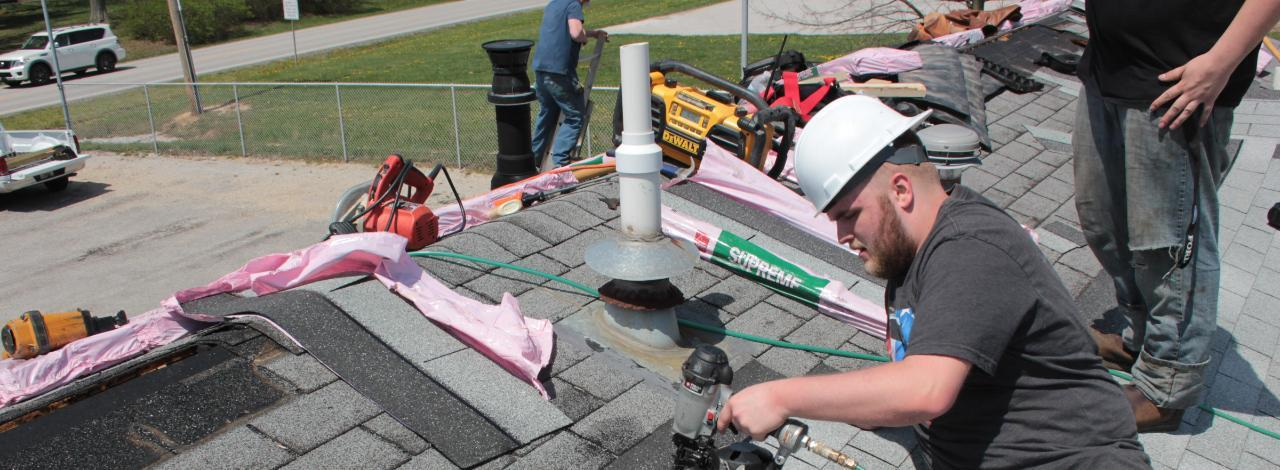 Student on roof operating nail gun to attach shingle to a roof