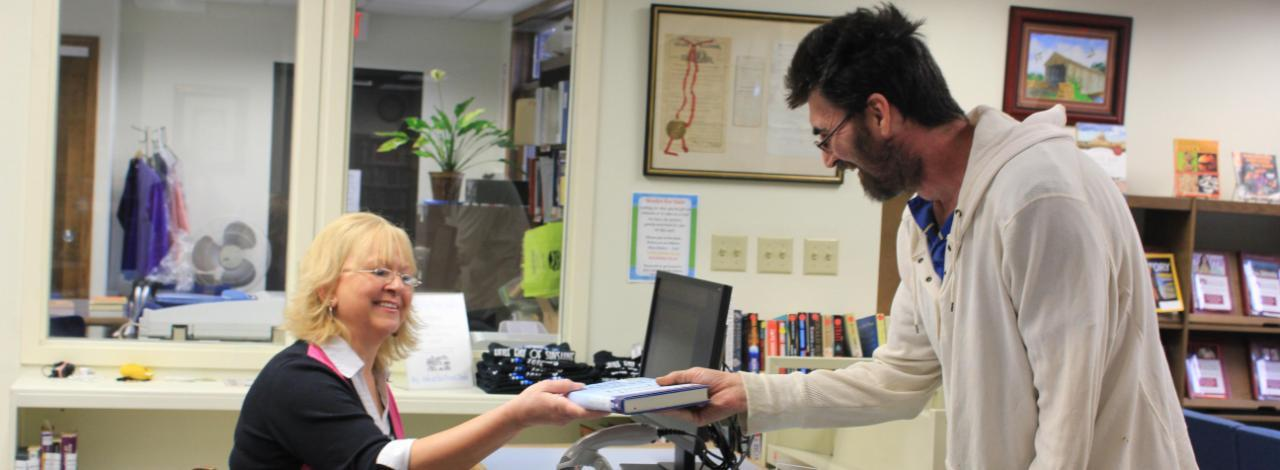 Librarian helping student check out a book
