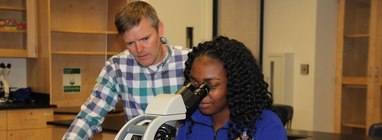 Student looking into a microscope with Bruce Fink