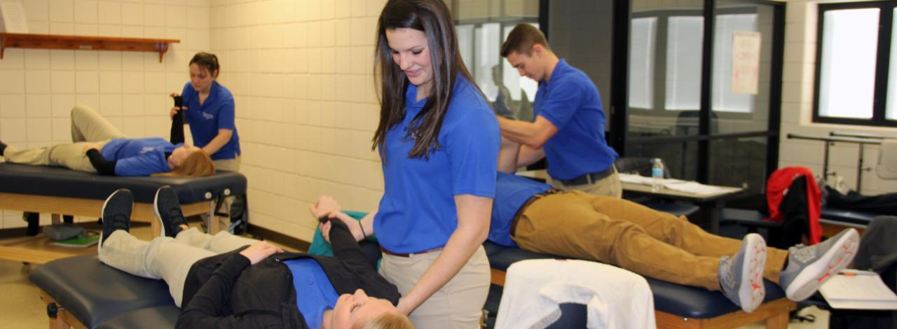 Physical Therapy student moving arm of a student who is lying on a table.