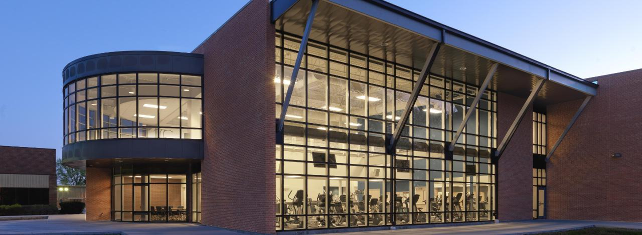 View of KC Fitness Center from outside at night.