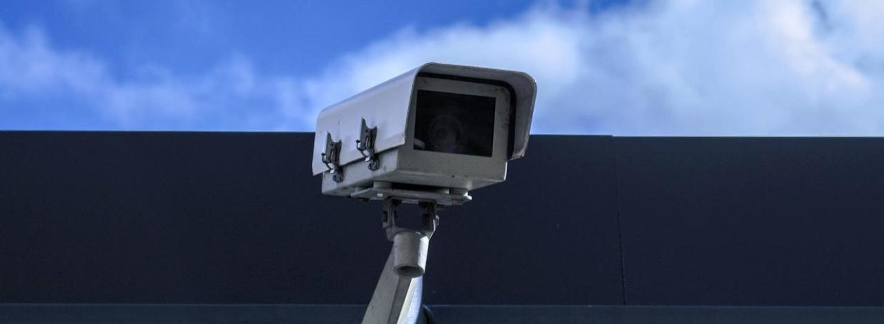 Security camera attached to the side of a building