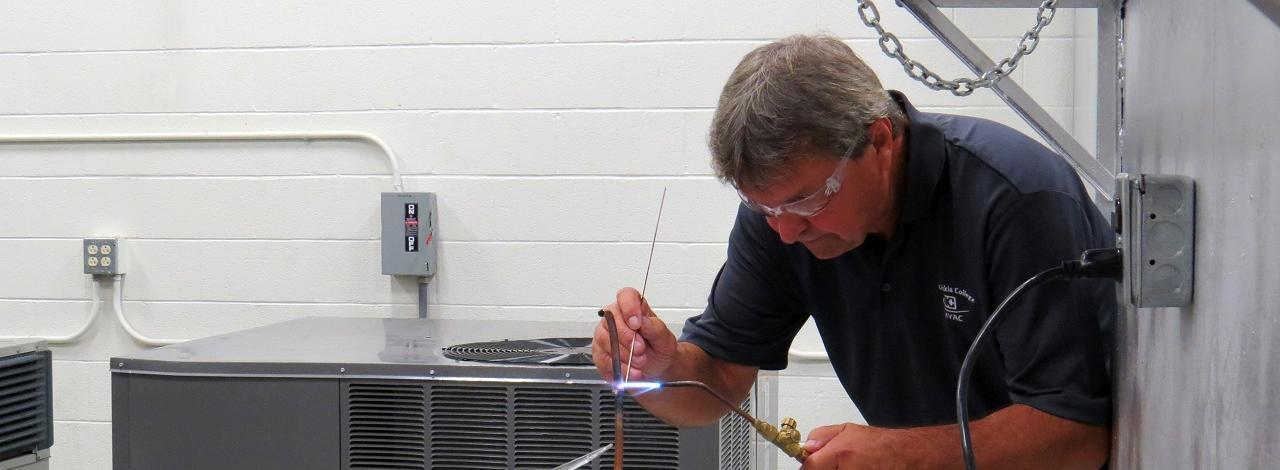 Student in the heating, ventilation and air conditioning class soldering a copper pipe.