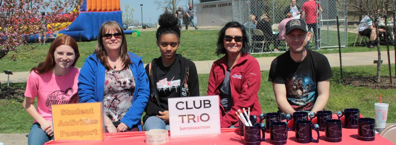Trio Club students with table at college spring picnic