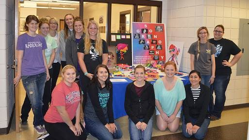 Sonography students posing with display for sonography month.